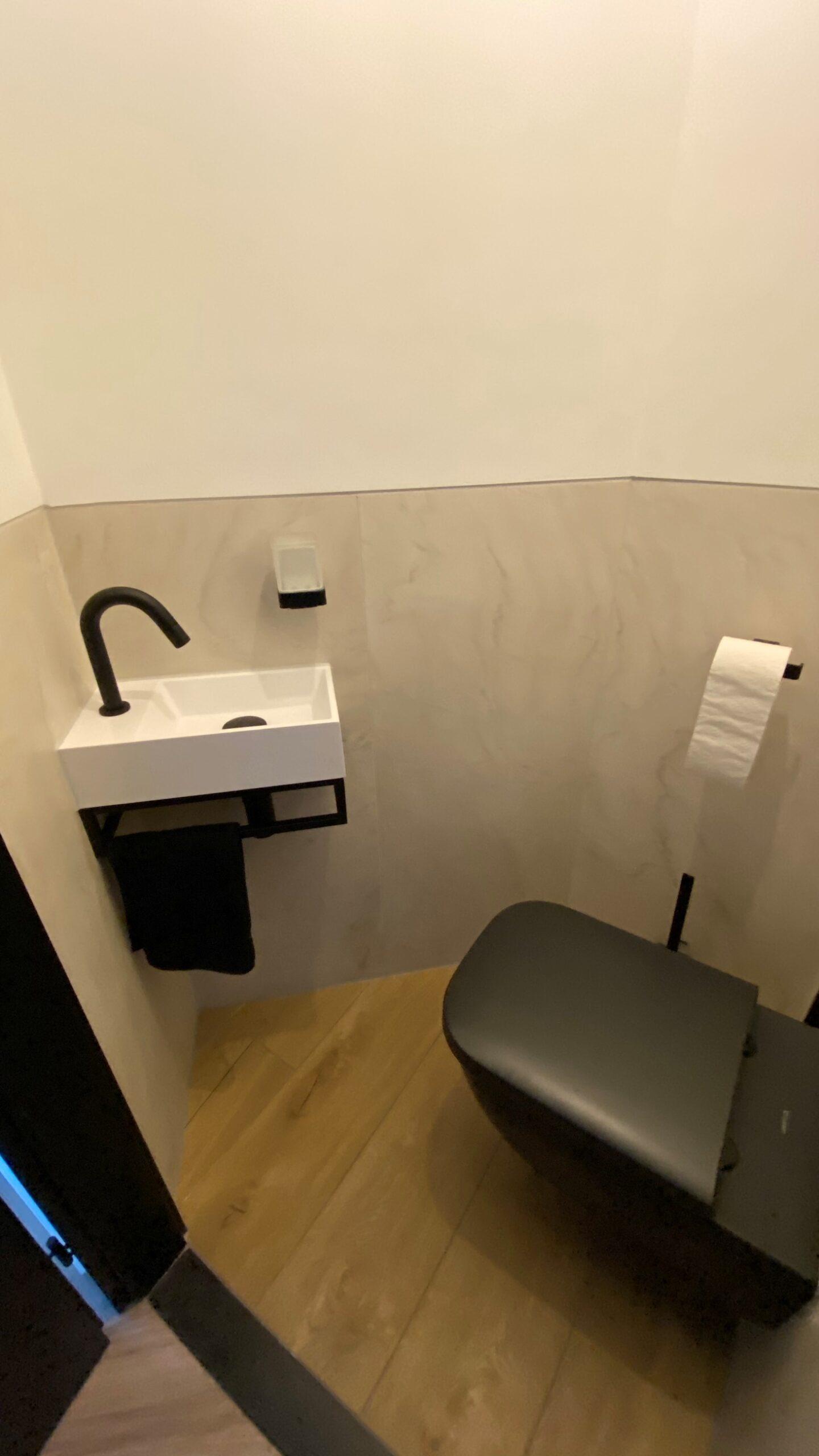 Onlangs hebben onze vakmannen weer een prachtige badkamer gerealiseerd. Deze designbadkamer kenmerkt zich door de natuurlijke materialen en de strakke accenten. De keramische houtlook vloertegel en de marmerlook wandtegel brengen alle matzwarte accenten nog meer naar boven. Natuurlijke materialen zoals marmer en hout brengen veel warmte aan de badkamer. De matzwarte accenten zorgen er voor dat het design wel intact blijft.